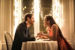 Una giovane coppia si tiene per mano al ristorante