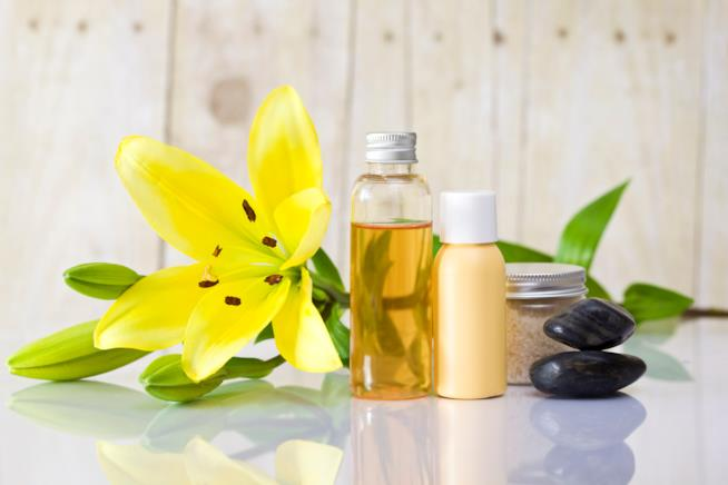 Tre flaconi di prodotti, olio, crema e scrub, due sassi neri, un fiore giallo appoggiato vicino