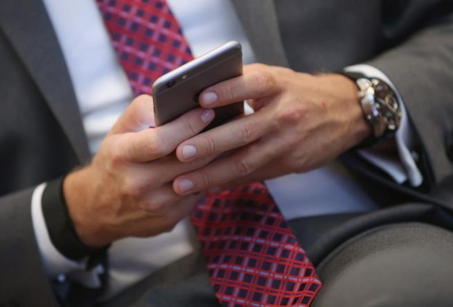 Un uomo con un cellulare in mano.