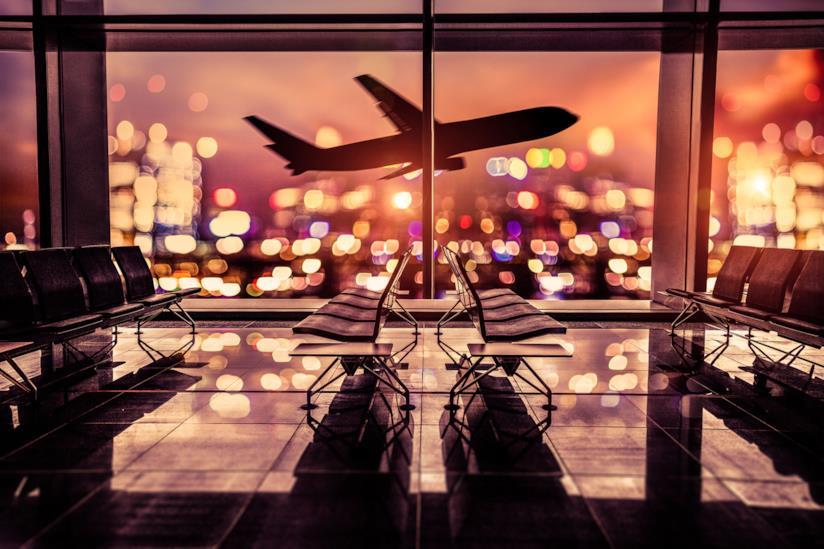 Un aereo decolla oltre la vetrata dell'aeroporto