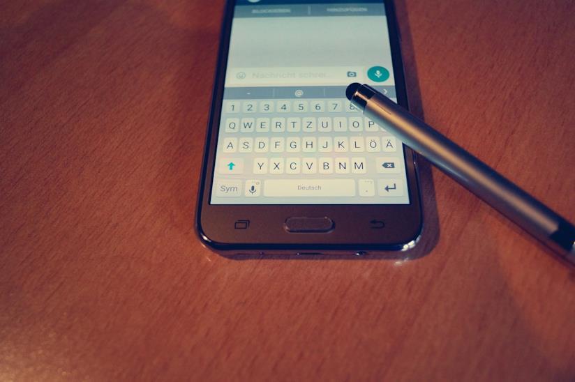 Uno smartphone con dietro uno sfondo marrone.