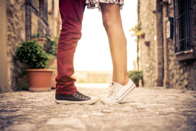gambe e scarpe sportive di un ragazzo e una ragazza, uno di fronte all'altro, lei in punta di piedi