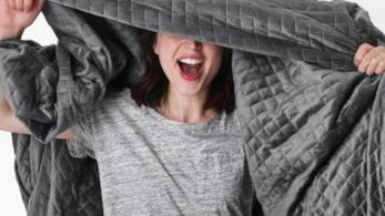 Una ragazza con una t-shirt grigia si copre con una gravity blanket