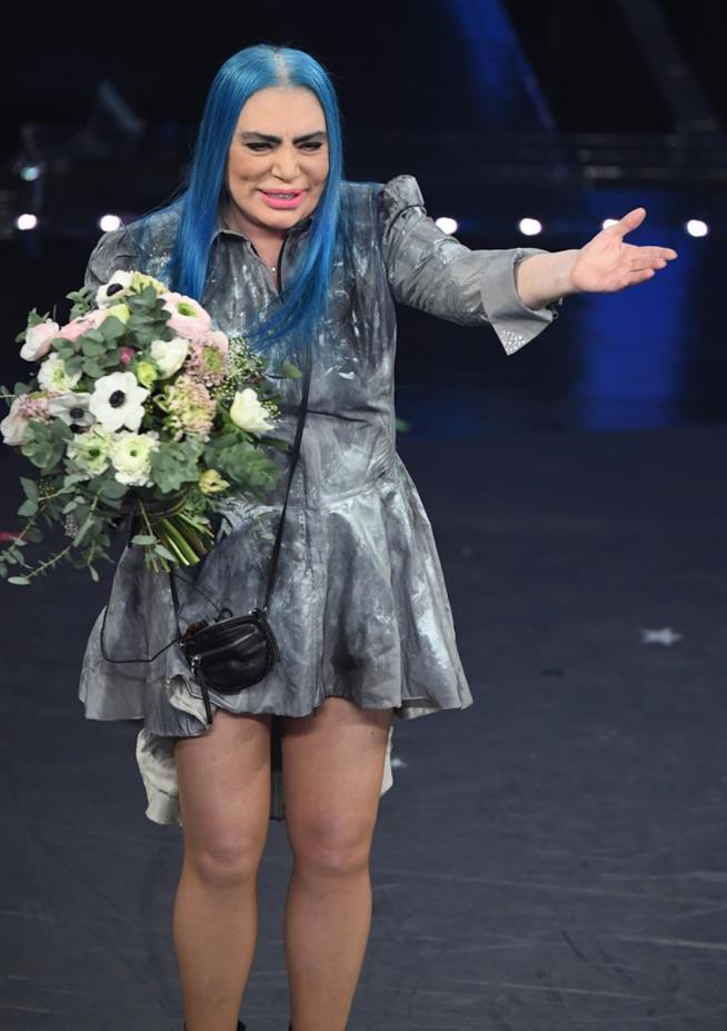 Loredana Berté in piedi, con un mazzo di fiori in mano e un vestito grigio