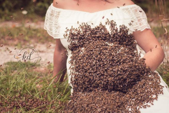Il pancione di una futura mamma coperto di api