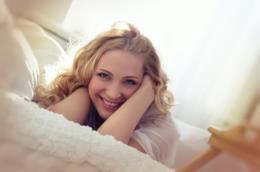 Ragazza che sorride sul letto al mattino
