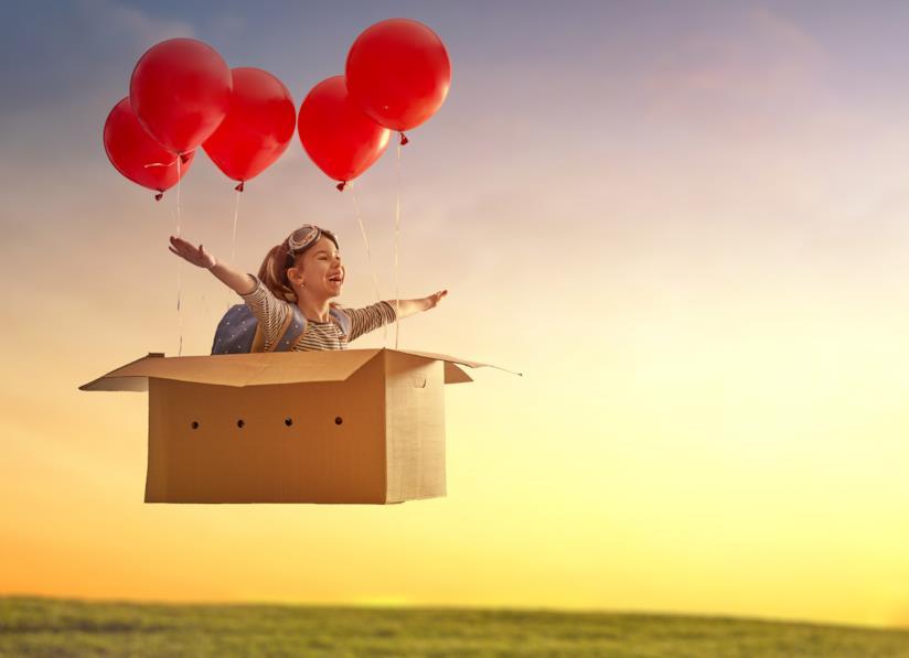 Una bambina in una scatola di cartone che vola grazie a dei palloncini rossi.