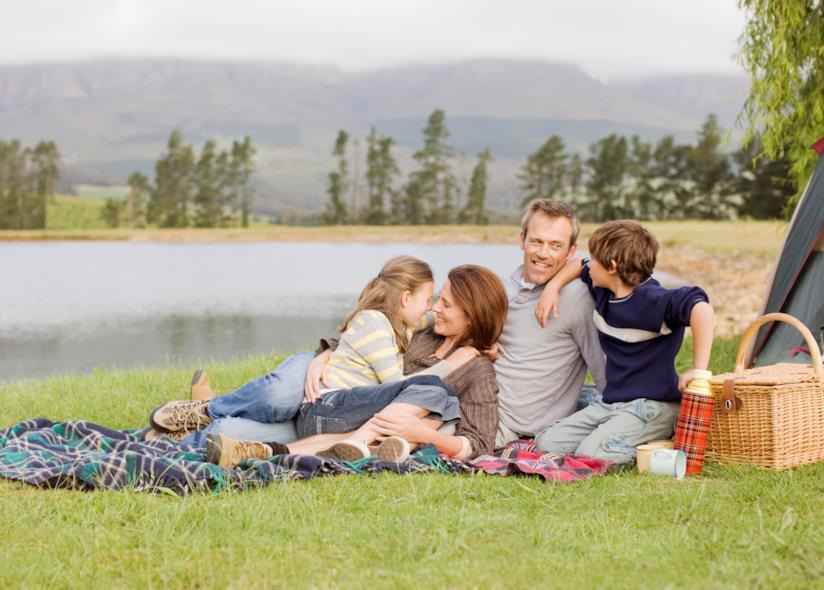 Famiglia fa un pic-nic in riva al lago