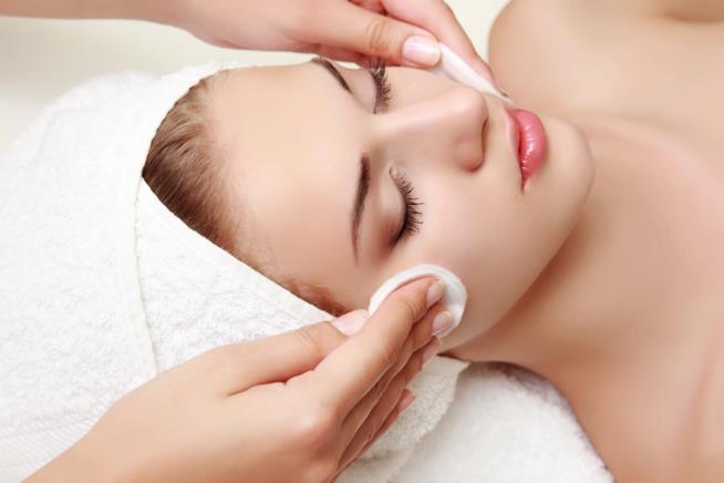 Una ragazza si fa detergere il viso con del cotone mentre è distesa e rilassata