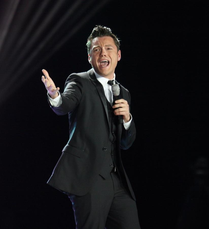 Tiziano Ferro, in piedi, vestito di nero, con il microfono in mano
