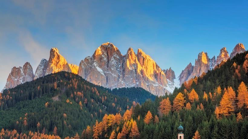 Valle di montagna in autunno con alberi verdi e arancioni