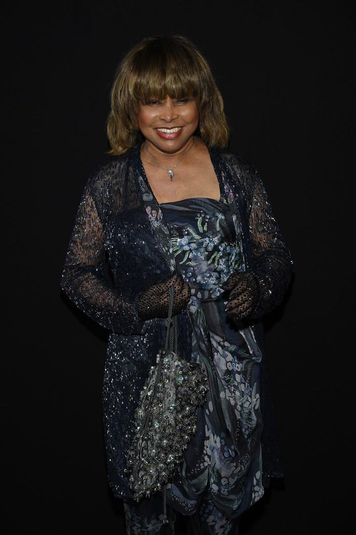 Tina Turner, elegante, in nero, in piedi, su sfondo nero