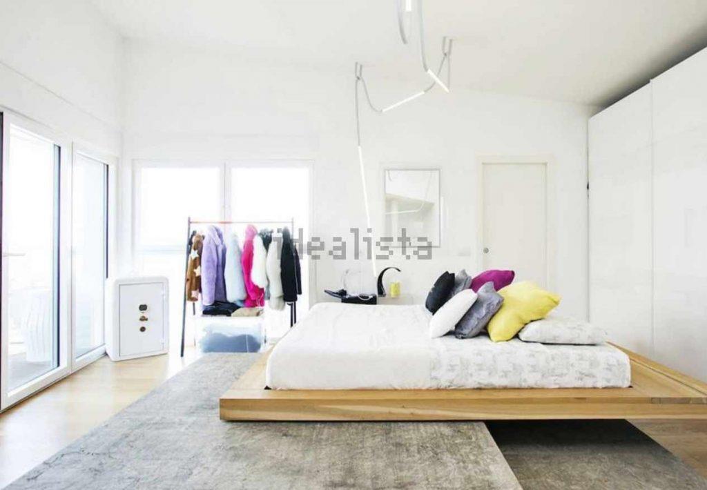 Il letto con diversi cuscini e alcuni abiti