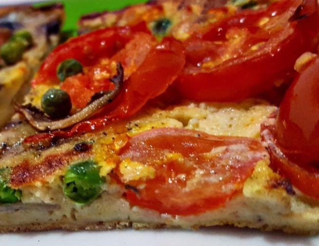Spicchio di pizza con pomodori e piselli