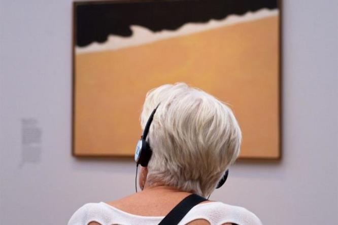 Una donna con delle cuffie seduta di fronte ad un quadro