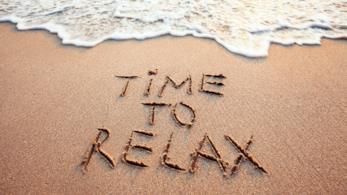 sabbia e un'onda a riva che si avvicina alla scritta time to relax
