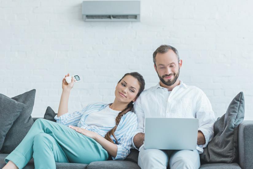 Coppia seduta sul divano a casa con l'aria condizionata accesa