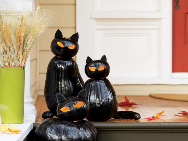 Tre lanterne zucca a gatto fuori il portico di una casa