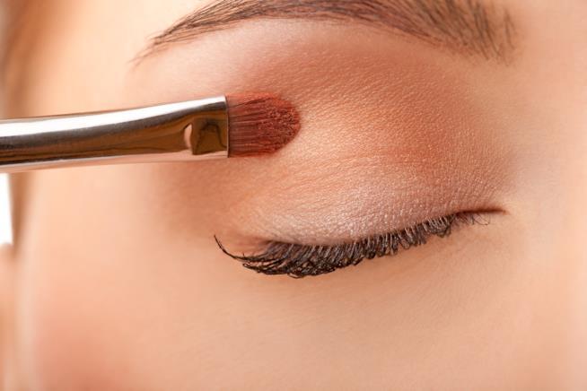 Dettaglio di un occhio mentre viene applicato un ombretto