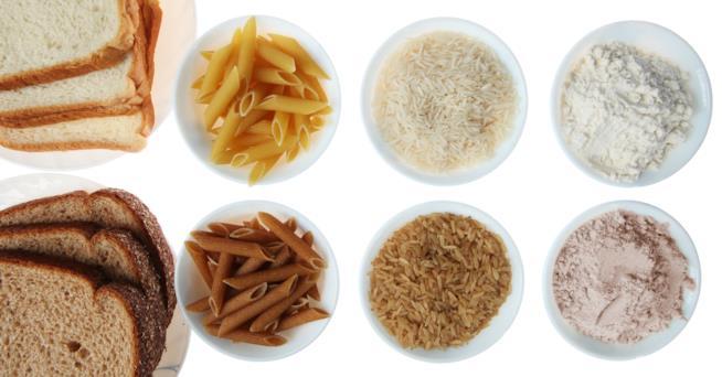 Inquadratura dall'alto di ciotole piene di pane, pasta, riso e farine misti