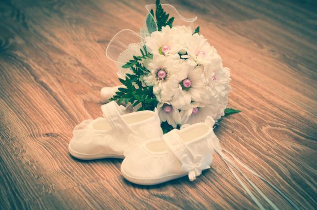 Scarpette di neonato accanto a un mazzo di fiori
