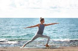 Una donna fa yoga in spiaggia