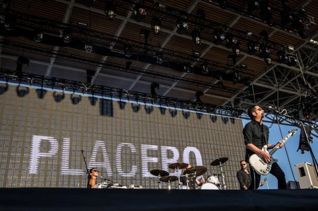 La scritta Placebo sullo schermo, la tastierista, una batteria e il chitarrista in piedi