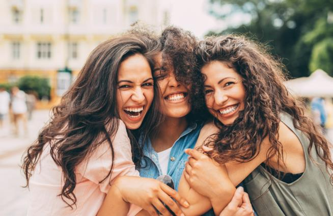Tre ragazze si abbracciano sorridendo