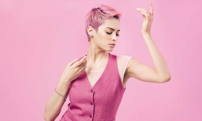Elodie, vestita di rosa, con i capelli rosa e su sfondo rosa