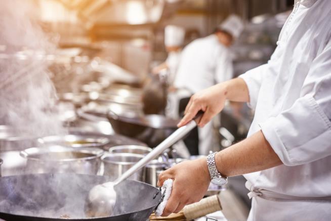 Un cuoco gira gli alimenti in padella