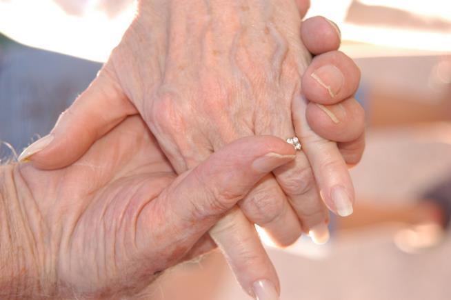 Mani di uomo e donna anziani strette l'una all'altra