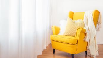 Una bella poltrona gialla con dei cuscini e una coperta vicino a una finestra