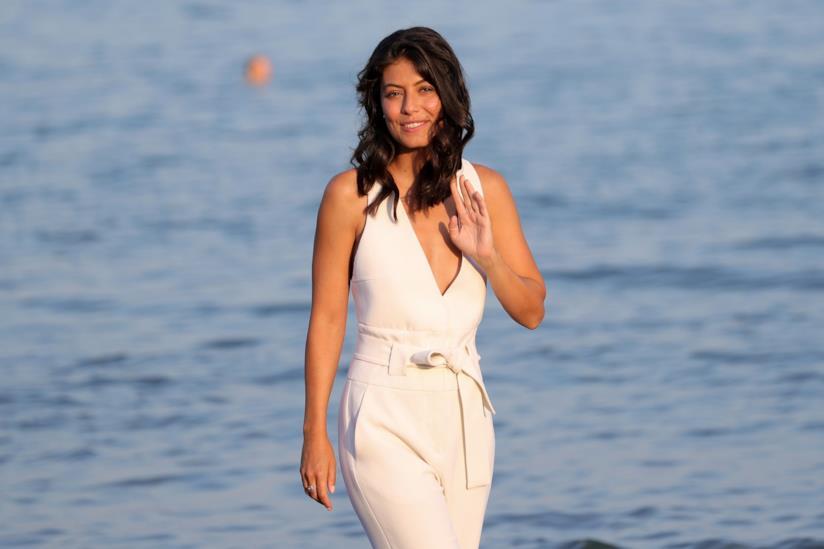 Alessandra Mastronardi, in piedi, indossa una tuta bianca, con lo sfondo del mare