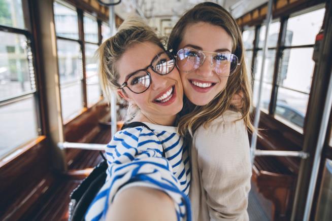 Due ragazze si scattano un selfie su un autobus