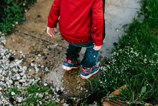 Bambino che salta nelle pozzanghere