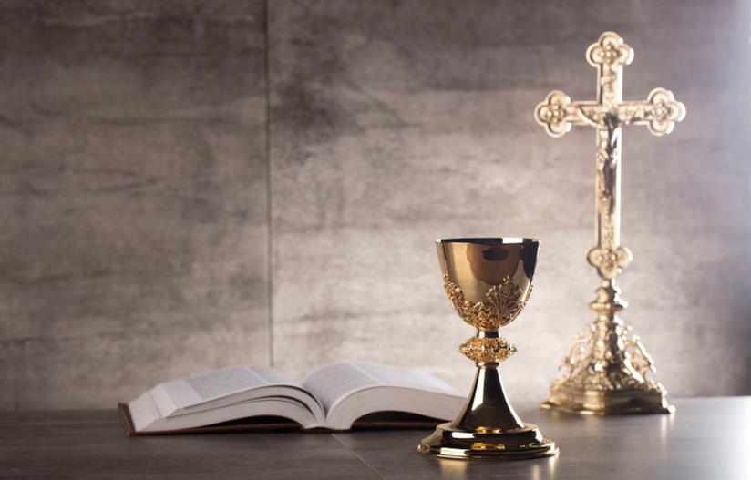 Calice sacro e bibbia su un tavolo