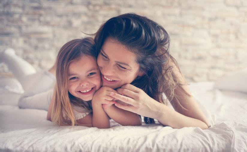 Madre e figlia abbracciate sul letto