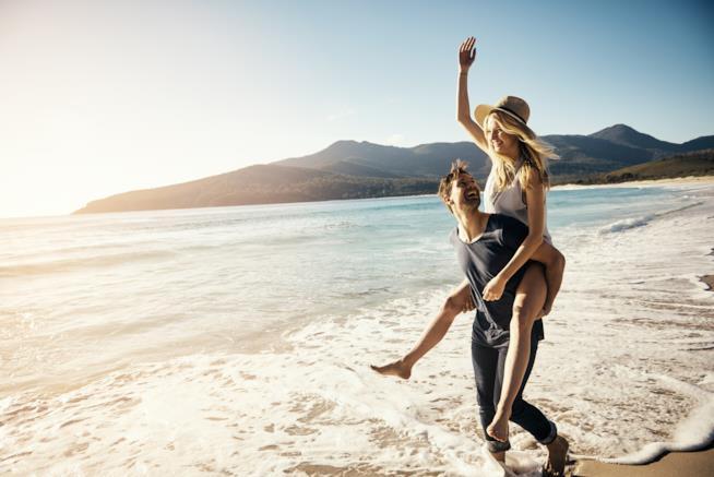 Una coppia passeggia sulla riva del mare