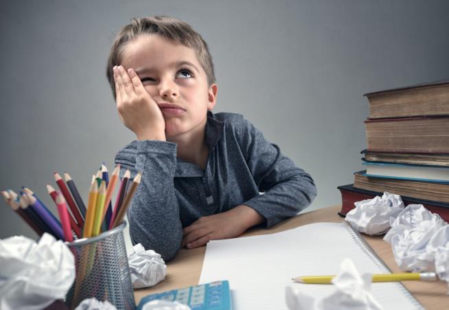 Bambino che fa i compiti in difficoltà
