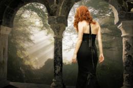 Una donna di spalle con un vestito nero e i capelli rossi.