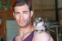 Il veterinario Evan Antin con un volatile sulla spalla