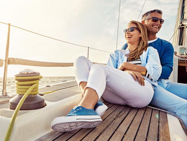 Una coppia sorride abbracciata su una barca a vela