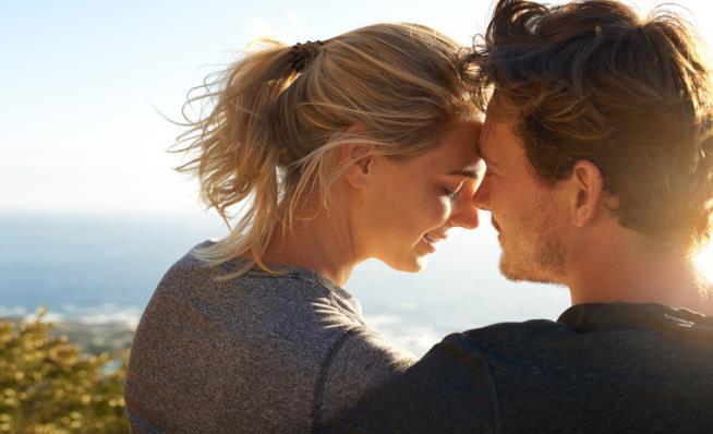 Un ragazzo e una ragazza sono seduti fronte a fronte su un promontorio