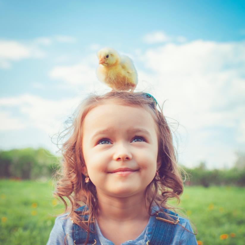 Bambina con un pulcino sulla testa
