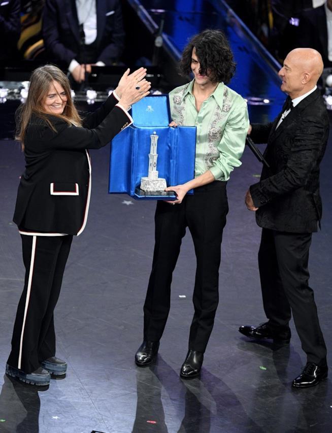 Motta in piedi, con il mano il premio consegnatogli da Claudio Bisio, applaudito da Nada