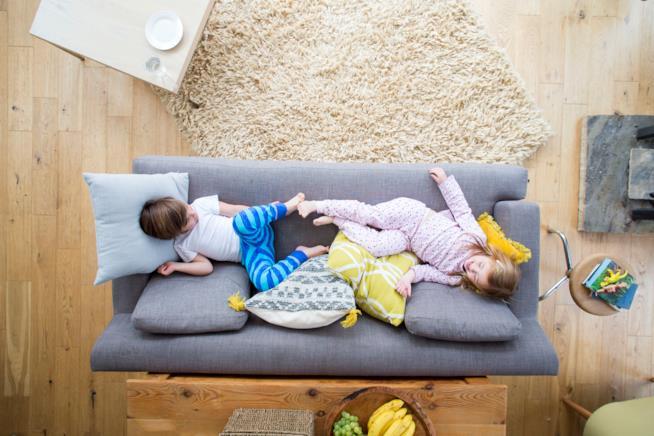 Bimbi che giocano sul divano del soggiorno