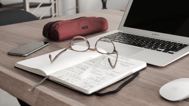 Un computer, un quaderno, un paio di occhiali, un astuccio e un cellulare