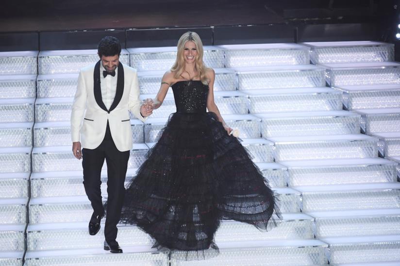 Michelle Hunziker con un lungo abito nero e Pierfrancesco Favino con una giacca bianca e pantaloni neri scendono la scalinata dell'Ariston