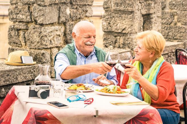 Coppia di anziani che mangia e brinda allegra