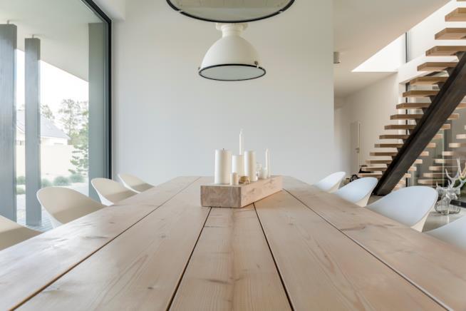 tavolo da pranzo in soggiorno illuminato da una coppia di lampade a sospensione
